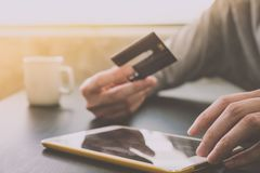 Male hands holding credit card and using Tablet with a cup of coffee on the table.Online shopping concept. Male hands holding credit card and using Tablet with Royalty Free Stock Image