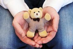 Male hands holding a cute teddy bear. Man hands in white mittens showing a teddy bear gift dresses in knitted hat and scarf royalty free stock photos