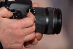 Male hands holding a digital SLR camera close up stock images