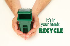 Male hands holding a garbage container. Male hands holding an open garbage can, it's in your hands recycle Royalty Free Stock Image