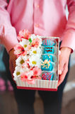 Male hands holding gift box filled with flowers and fruit candy Royalty Free Stock Photos