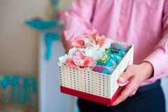 Male hands holding gift box filled with flowers and fruit candy Royalty Free Stock Images
