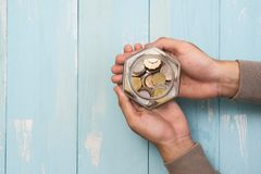 Male hands holding glass jar with coins inside. Top view Royalty Free Stock Images