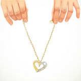 Male hands holding gold chain with pendant-heart Royalty Free Stock Images