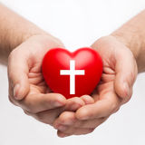 Male hands holding heart with cross symbol Royalty Free Stock Images
