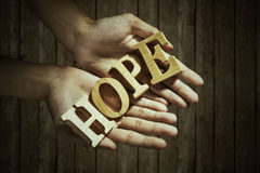 Male hands holding hope. Closeup of male hands holding a word of HOPE royalty free stock images