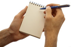 Male hands holding pad and pen isolated on a white. The man wrote in his notebook, keeping it in his hands. Close-up on a white background royalty free stock image