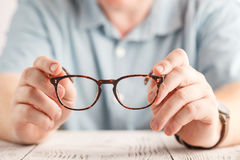 Male hands holding a pair of glasses Royalty Free Stock Photography