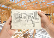 Male Hands Holding Pen and Pad of Paper with Custom Kitchen Illustration Inside Construction Framing. stock image