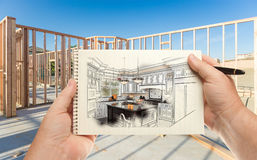 Male Hands Holding Pen and Pad of Paper with Custom Kitchen Illu. Stration Inside Construction Framing Stock Photos