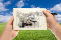 Male Hands Holding Pen and Pad of Paper Up with Custom Kitchen I. Llustration Outside Near Grass Field and Blue Sky Stock Photos