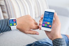 Male hands holding phone smart watch with app smart home. Male hands holding touch phone and smart watch with app smart home on screen Royalty Free Stock Photography