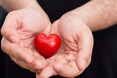 Male hands holding red heart closeup, on black. Background Royalty Free Stock Images