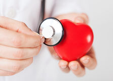 Male hands holding red heart and stethoscope. Healthcare and medicine concept - close up of male hands holding red heart and stethoscope stock photo