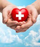 Male hands holding red heart with white cross. Family health, charity and medicine concept - close up of male hands holding red heart with white cross over blue Royalty Free Stock Photography