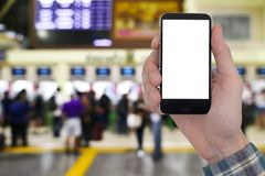 Male hands holding smart phone with touch blank white screen on. Blurred image of people buy ticket at the counter background Royalty Free Stock Image