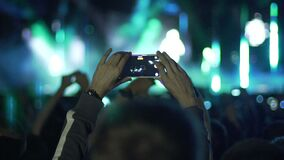 Male hands holding smartphone in air, filming amazing show on stage, slow-mo