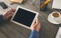 Male hands holding a tablet with blank screen. Man working in a home office Stock Photo