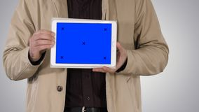 Male hands holding tablet with blue screen mockup on gradient background. stock photography