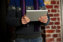 Male hands holding tablet computer near brick wall Stock Photos