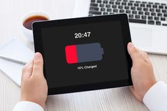 Male hands holding tablet with low charged battery on screen Royalty Free Stock Images