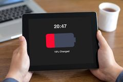 Male hands holding tablet with low charged battery on screen Stock Photography