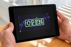 Open stock market concept on a tablet. Male hands holding a tablet with open stock market concept Stock Photo