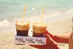 Male hands holding two ice frappe coffee on the beach near sea Stock Images