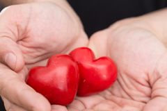 Male hands holding two red hearts, closeup. Background Royalty Free Stock Photography