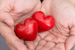 Male hands holding two red hearts, closeup. Background Royalty Free Stock Image