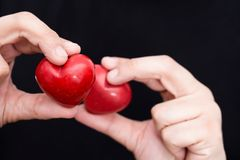 Male hands holding two red hearts, closeup. On black background Stock Photos