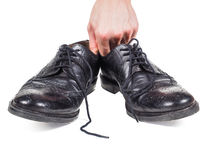 Male hands holding up a pair of worn black leather shoes Stock Photo