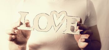 Male hands holding word Love at wall background Stock Images