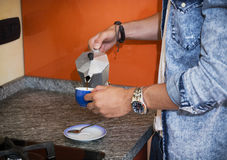 Male hands in home kitchen pouring espresso coffee from coffee-maker Stock Image