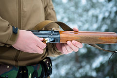 Male hands hunter inserted cartridge 12 caliber rifle on a backg. Round of pine forest in winter Stock Photography
