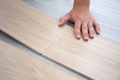 Male hands installing wood flooring Stock Image