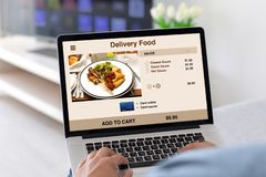 Male hands on keyboard laptop with app delivery food. On the screen in the house in room stock images