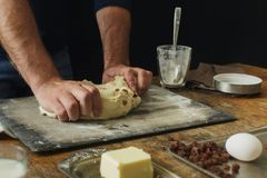 Male hands knead dough cooking cross buns home kitchen. Male hands knead the dough for cooking cross buns in a home kitchen Stock Photography