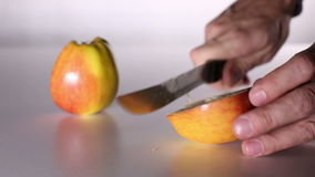 Male hands with a knife cut an apple in half. Apple is divided into two halves. Yellow apple with red sides stock video