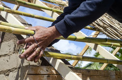 Male hands knotting reeds for a roof in green architecture Stock Photography