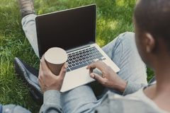Male hands with laptop and coffee closeup,over shoulder shot outdoors. Male hands with laptop and coffee cup closeup, over shoulder shot. African-american Stock Photos