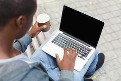 Male hands with laptop and coffee closeup,over shoulder shot outdoors. Male hands with laptop and coffee cup closeup, over shoulder shot. African-american Stock Photography