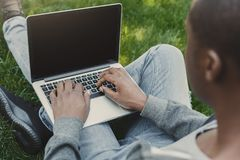 Male hands with laptop, over shoulder shot outdoors. Male hands with laptop closeup, over shoulder shot. African-american student working outdoors on computer Stock Images