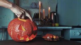 Male hands lights up candle inside jack o lantern then turns off light Halloween close up shot 4k stock video footage