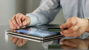 Male hands making online noncash payment on tablet, inserting bank card details Royalty Free Stock Photography