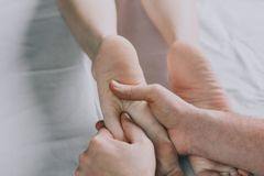 Male hands of a massage therapist do a woman foot massage. royalty free stock photo