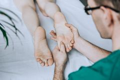 Male hands of a massage therapist does foot massage. stock photo
