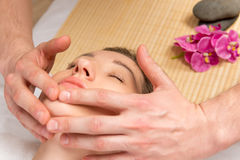 Male hands of the masseur, cosmetologist, doing massage the girl Stock Image