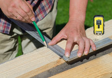 Male hands measuring wooden plank Royalty Free Stock Photos