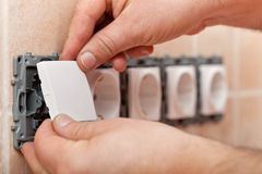 Male hands mounting electrical wall socket - closeup Stock Photography